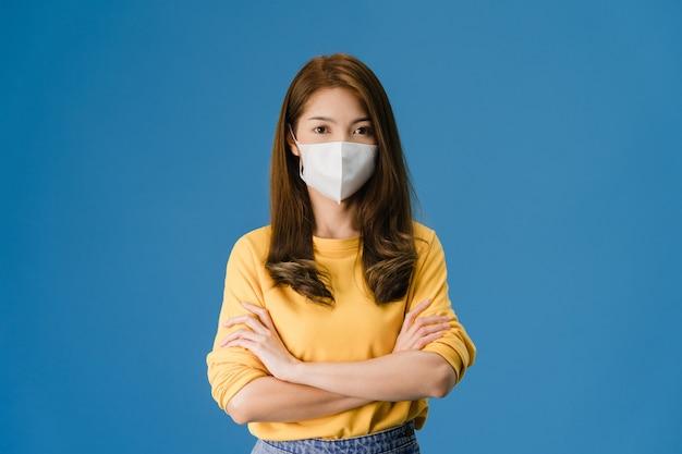 Chica joven de asia con mascarilla médica con los brazos cruzados, vestida con ropa casual y mirando a cámara aislada sobre fondo azul. autoaislamiento, distanciamiento social, cuarentena por coronavirus.
