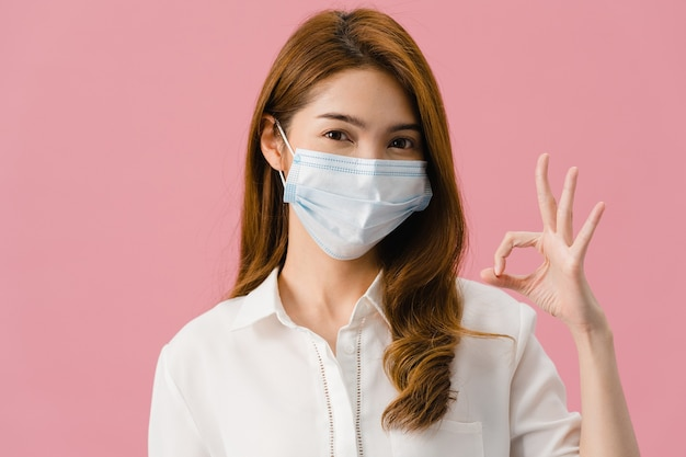 Chica joven de asia con mascarilla médica gesticulando signo ok vestido con ropa casual y mira a cámara aislada sobre fondo rosa.