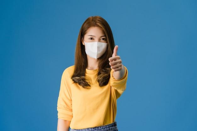 Chica joven de asia con mascarilla médica mostrando el pulgar hacia arriba vestida con un paño casual y mira a cámara aislada sobre fondo azul. autoaislamiento, distanciamiento social, cuarentena por coronavirus.