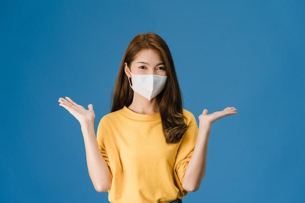 Chica joven de asia con mascarilla médica que muestra el signo de la paz, animar con vestida con ropa informal y mirando a cámara aislada sobre fondo azul. distanciamiento social, cuarentena por coronavirus.