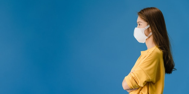 Chica joven de asia con mascarilla médica vestida con ropa casual y mira el espacio en blanco aislado sobre fondo azul. distanciamiento social, cuarentena por coronavirus. fondo de banner panorámico.