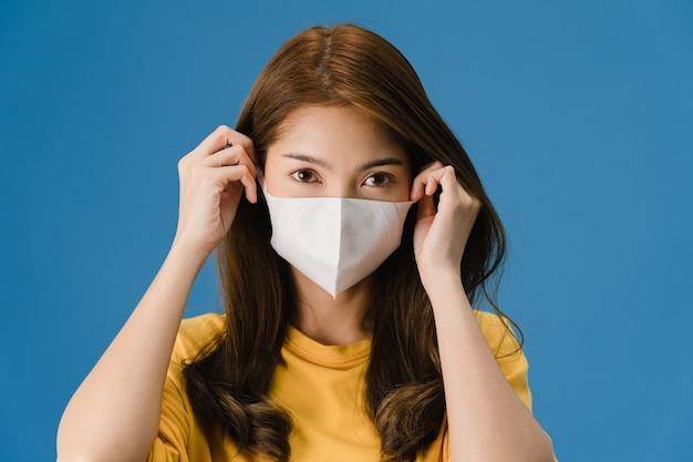 Chica joven de asia con mascarilla médica vestida con ropa casual y mirando a cámara aislada sobre fondo azul. autoaislamiento, distanciamiento social, cuarentena para la prevención del coronavirus.