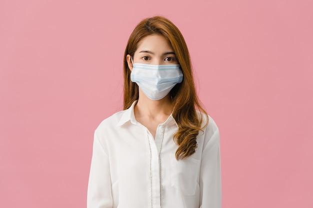 Chica joven de asia con mascarilla médica vestida con ropa casual y mirando a cámara aislada sobre fondo rosa.