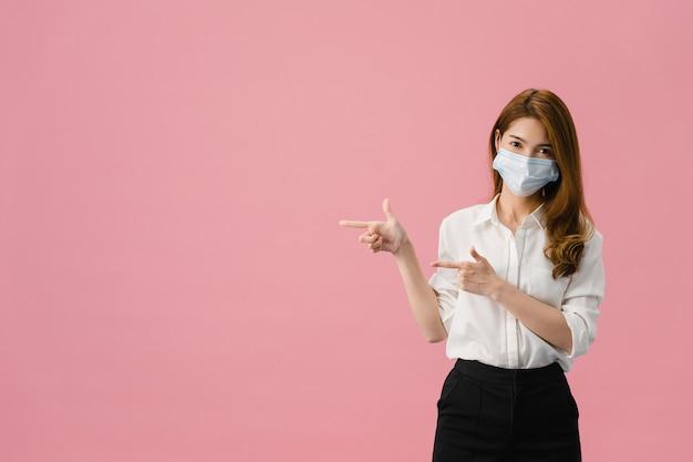 La chica joven de asia usa una mascarilla médica que muestra algo en el espacio en blanco con vestida con un paño informal y mira la cámara aislada sobre fondo azul.