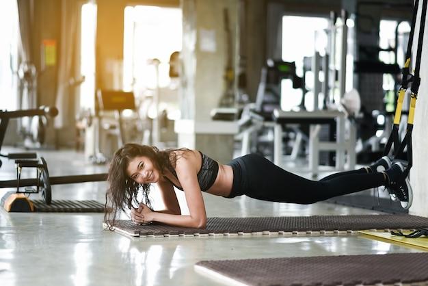 Chica joven asiática estirándose con trx en el gimnasio.