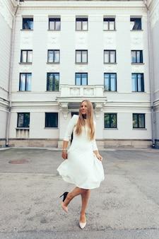 Chica joven de aspecto europeo con un vestido blanco en el fondo del edificio.
