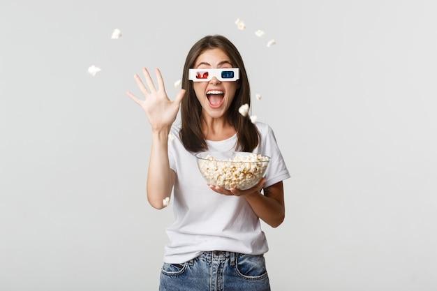 Chica joven atractiva alegre en gafas 3d, lanzando palomitas de maíz en la pantalla mientras ve la película.