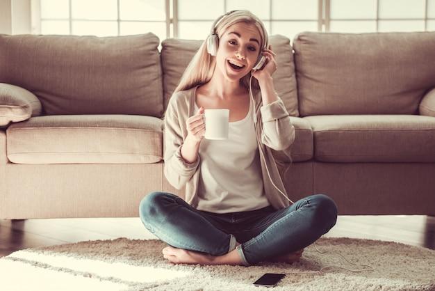 Chica joven atractiva en auriculares está escuchando música.