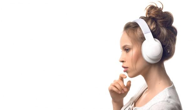 Chica joven atractiva con auriculares sobre pared blanca