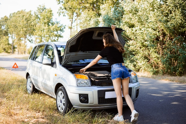 Chica joven y atractiva cerca de un capó abierto de un coche en el lateral intenta solucionar el problema