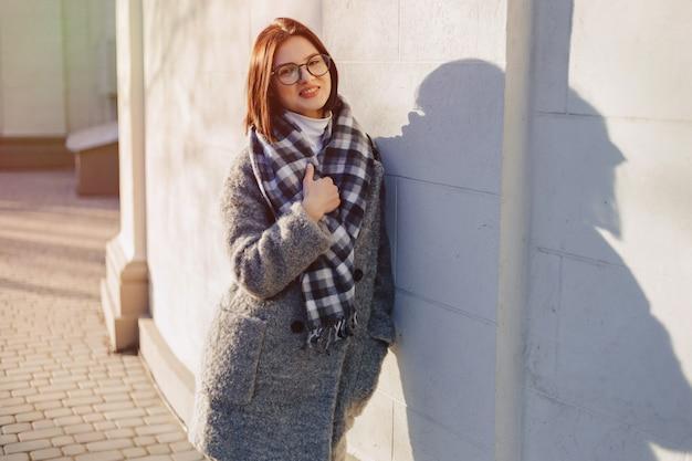 Chica joven atractiva con gafas en un abrigo caminando en un día soleado