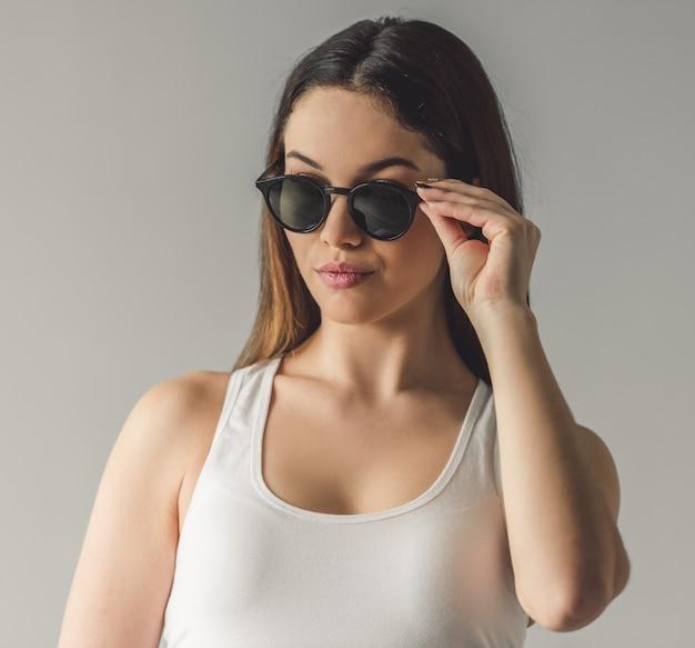 Chica joven atractiva en gafas de sol está mirando a otro lado.