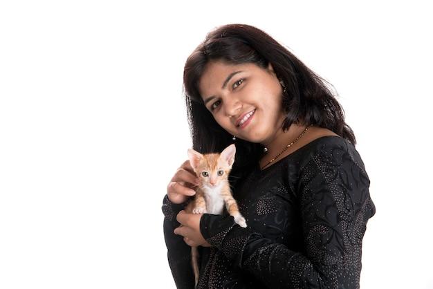 Chica joven atractiva con gato sobre fondo blanco.