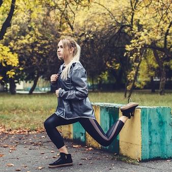 Chica joven atractiva haciendo ejercicios deportivos en un parque de la ciudad en clima lluvioso.