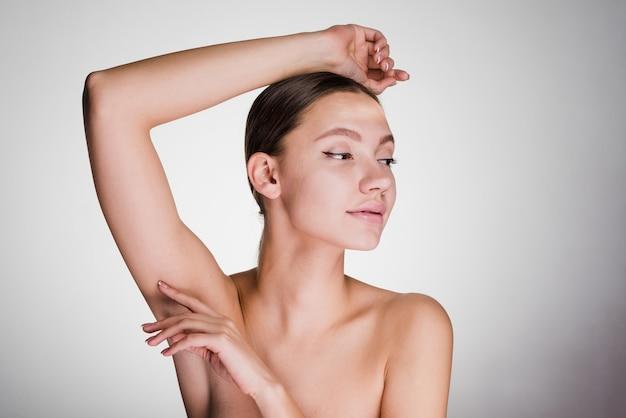 Chica joven atractiva mostrando sus axilas sin pelo