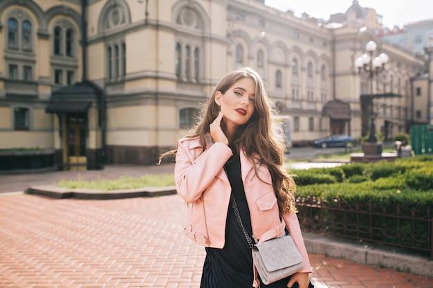 Chica joven atractiva con pelo largo y rizado y labios rojos posando en la ciudad.