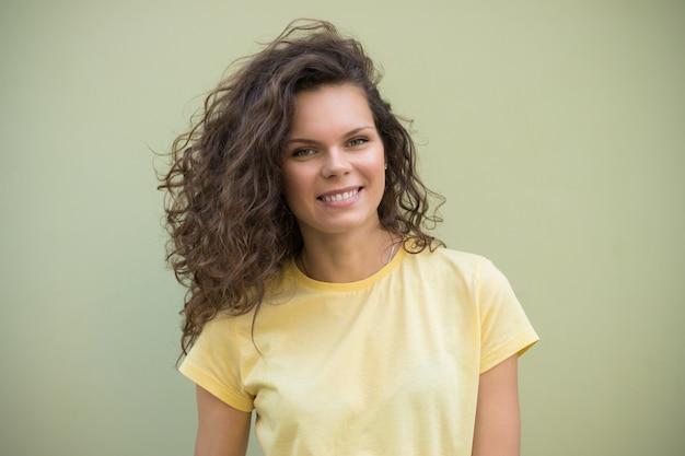 Chica joven atractiva con el pelo rizado marrón que se coloca en una camiseta amarilla contra una pared verde
