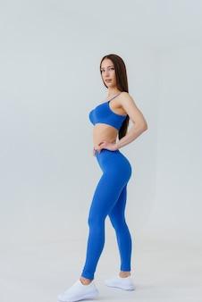 Chica joven atractiva que presenta en un chándal azul en una pared blanca. fitness, estilo de vida saludable.