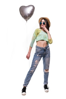 Chica joven atractiva que sostiene el globo de helio del día de san valentín aislado en blanco