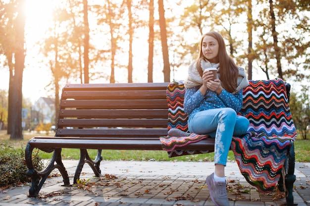 Chica joven y atractiva sentada en un banco en el parque otoño y tomando café