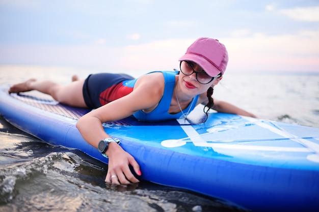 Chica joven atractiva con tabla de sup en el fondo del mar y la puesta del sol