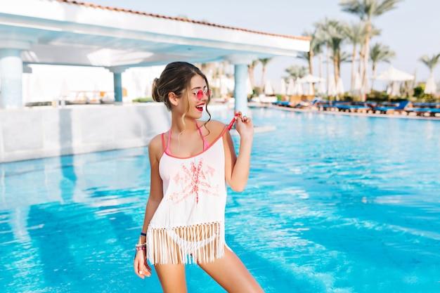 Chica joven atractiva en vestido de playa de pie frente a la piscina al aire libre con palmeras en el fondo y mirando a otro lado