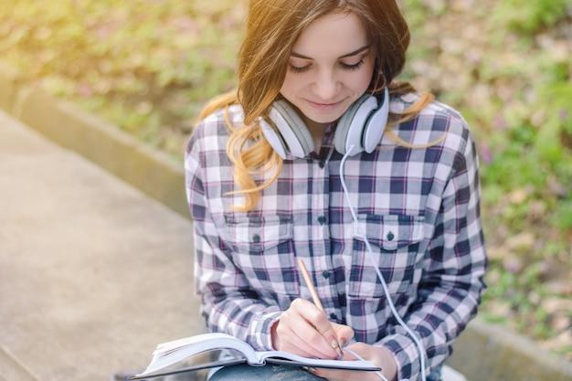 Chica joven en auriculares de camisa a cuadros escribiendo en el cuaderno