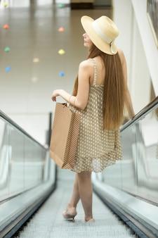 Chica joven bajando por unas escaleras mecánicas
