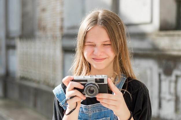 Chica joven bastante linda que sostiene la cámara retra