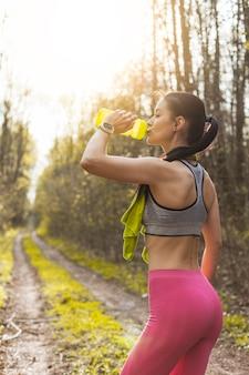 Chica joven bebiendo agua en la naturaleza