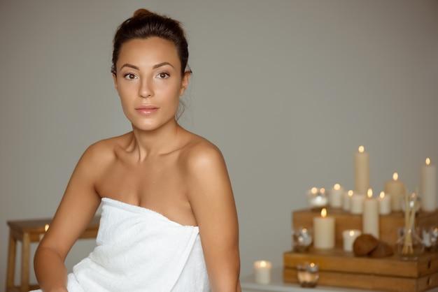 Chica joven y bella relajante en el salón de spa.