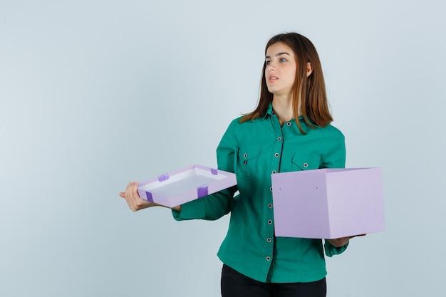 Chica joven en blusa verde, pantalón negro abriendo caja de regalo, mirando a otro lado y mirando enfocado, vista frontal.