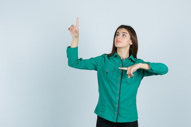 Chica joven en blusa verde, pantalón negro apuntando hacia arriba y hacia la izquierda con el dedo índice y mirando enfocado, vista frontal.