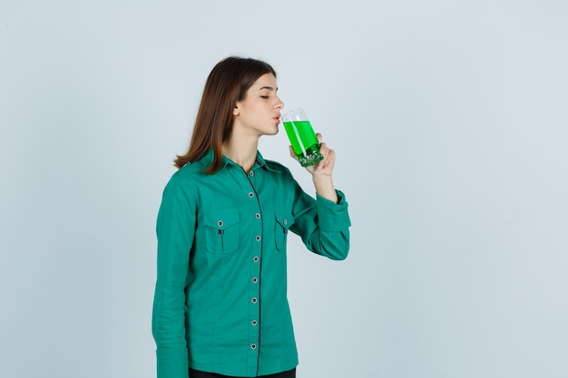 Chica joven en blusa verde, pantalón negro bebiendo un vaso de líquido verde y mirando enfocado, vista frontal.
