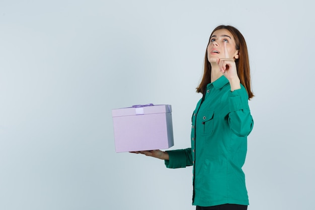 Chica joven en blusa verde, pantalón negro con caja de regalo, apuntando hacia arriba con el dedo índice y mirando enfocado, vista frontal.