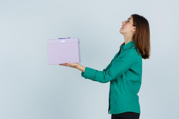 Chica joven en blusa verde, pantalón negro con caja de regalo, mirando hacia arriba y mirando enfocado, vista frontal.