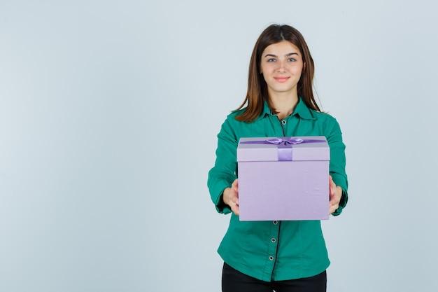 Chica joven en blusa verde, pantalón negro dando caja de regalo y mirando feliz, vista frontal.