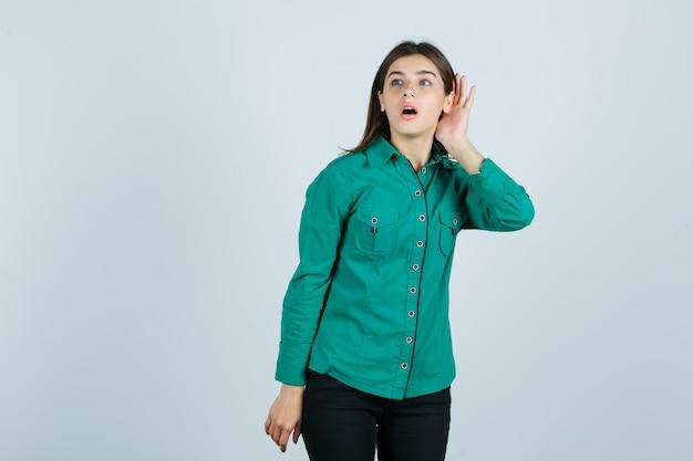 Chica joven en blusa verde, pantalón negro sosteniendo la mano cerca de la oreja para escuchar algo y mirando enfocado, vista frontal.