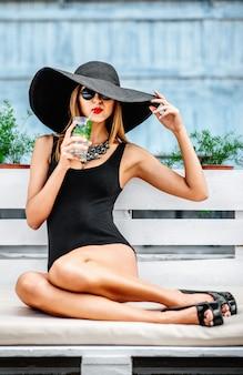 Chica joven bonita bebe el coctail frío al aire libre en café de la playa