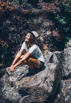 Una chica joven y bonita cierra los ojos con el sombrero puesto mientras toma el sol en las montañas.