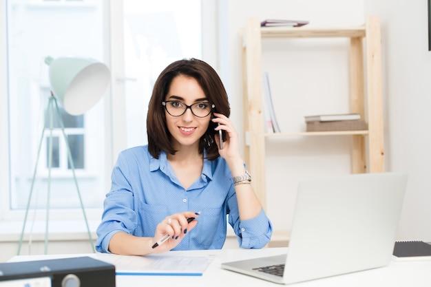 Una chica joven y bonita está sentada a la mesa en la oficina. ella tiene camisa azul y lentes negros. ella está hablando por teléfono y sonriendo a la cámara.