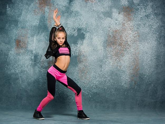 Chica joven break dance en la pared.