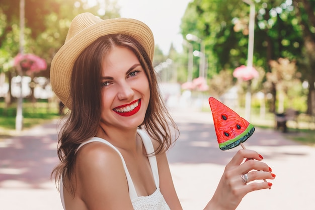 Chica joven de buen humor camina en el parque y sonríe. dulce niña feliz en sombrero de paja camina en el parque con una paleta en forma de sandía