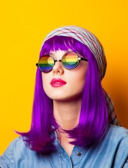 Chica joven con cabello morado y arco iris en suglasses en amarillo
