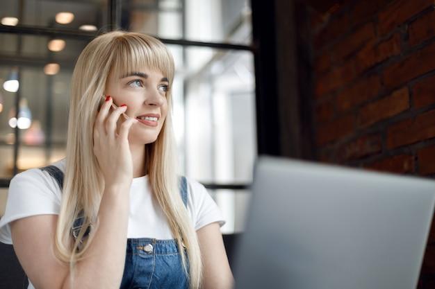 Chica joven en la cafetería tomando café y usando el teléfono móvil. las compras en línea