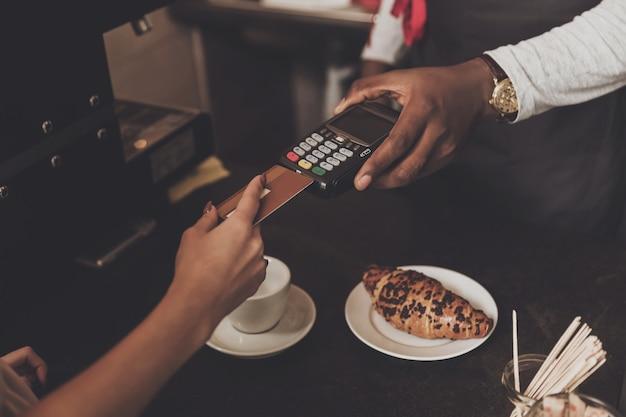 Chica joven se calcula el café con tarjeta de crédito.