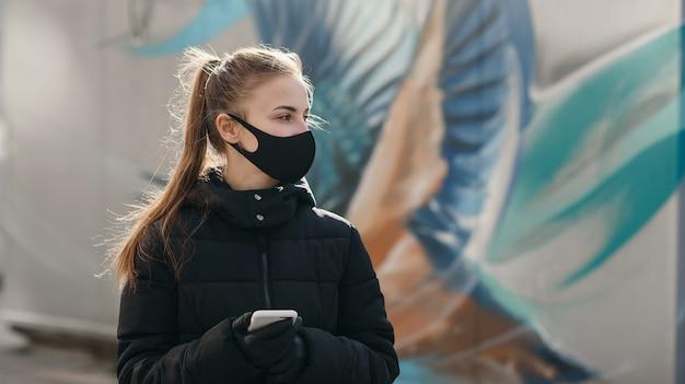 Chica joven en la calle de la ciudad con mascarilla médica estéril negro. mujer que usa el teléfono para buscar noticias sobre ncov 2019. cuarentena covid-19 pandemia de epidemia de coronavirus y concepto de salud