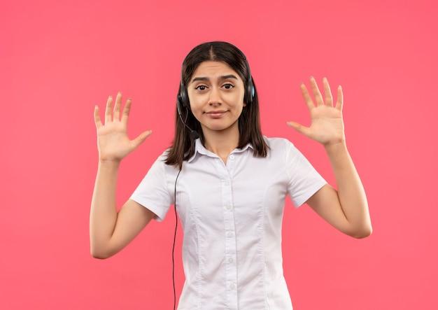Chica joven con camisa blanca y auriculares, levantando las manos en señal de rendición mirando confundido parado sobre la pared rosa