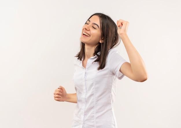 Chica joven en camisa blanca feliz y positiva con los ojos cerrados de pie sobre la pared blanca