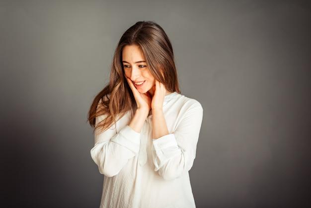 Chica joven en una camisa blanca en una pared gris. mujer francesa en blusa blanca contra una pared de paredes grises. sin retoques. sin maquillaje.